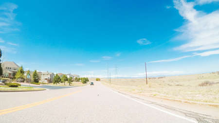 POV- Driving on paved road in suburban neighborhood in Colorado. 版權商用圖片