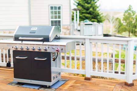 Six burner outdoor gas grill with open lid on back patio. Banco de Imagens