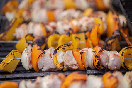 Step by step. Cooking chicken shish kabobs with bell peppers and yellow onions on outdoor gas grill.