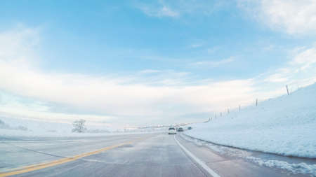 Driving on suburban road after Spring snow storm. Stock Photo