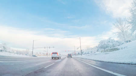 Denver, Colorado, USA-March 19, 2018-POV-Driving on suburban road after Spring snow storm. 報道画像