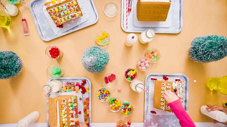 Flat lay. Kids decorating small gingerbread houses at the Christmas craft party. Banco de Imagens