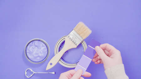 Opened metal paint can with violet paint and paint swatches.
