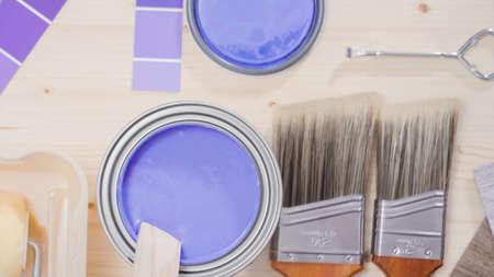 Mixing new purple  paint with wooden paint stick. Reklamní fotografie