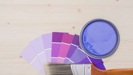 Variety of paint swatches with shades of purple pain on unfinished wooden background.