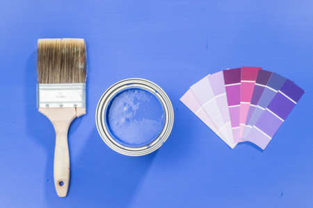 Upened metal paint can with purple paint and paint brush. Reklamní fotografie