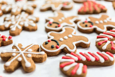 Decorating traditional gingerbread cookies with royal icing for Christmas. Stock Photo