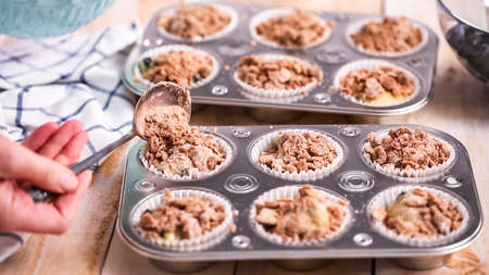 Scooping cinnamon and sugar topping on blueberry muffin batter. Stock Photo