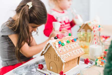 Kinder schmücken kleine Lebkuchenhäuser bei der Weihnachtsbastelparty. Standard-Bild