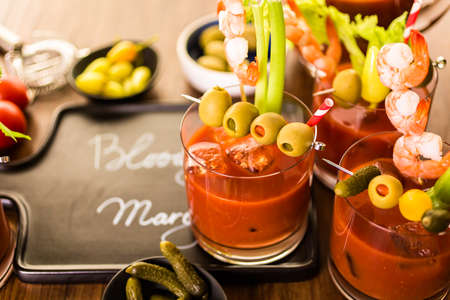 Bloody mary cocktail garnished with olives, pickles, and cocktail shrimp. Imagens