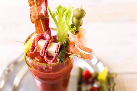 Bloody mary cocktail garnished with celery sticks, olives, and bacon strips.