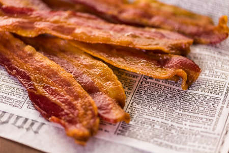 Cooked bacon strips on a newspaper.
