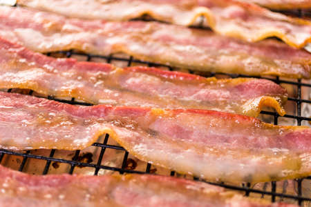 Cooked bacon strips on a baking sheet.