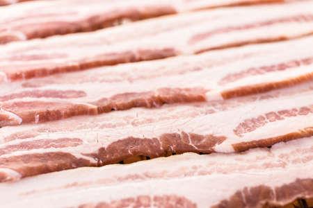 Raw bacon strips on a baking sheet.