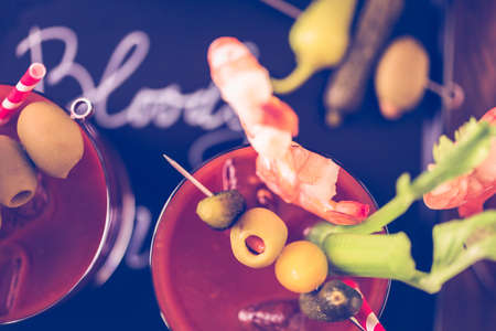 Bloody mary cocktail garnished with olives, pickles, and cocktail shrimp. Banco de Imagens