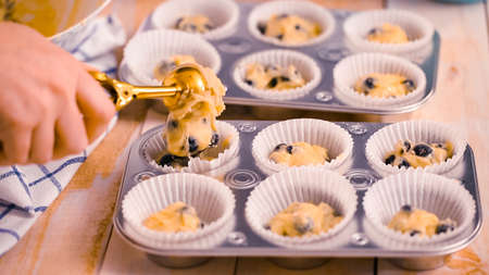 Scooping blueberry muffin batter into metal muffin pan.