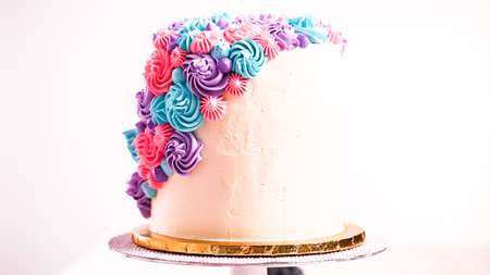 Baker piping pastel color buttercream rosettes on a white cake to make a unicorn cake. Stock Photo