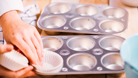 Lining metal muffin pan with paper cupcake liners to bake blueberry muffins. Фото со стока