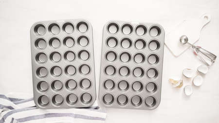 Flat lay. Lining cupcake pan with paper cupcake liners. Imagens