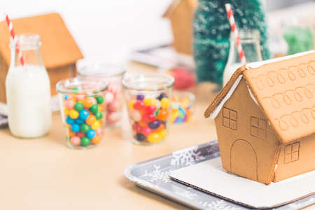 Kids party to decorate small gingerbread houses  with candies.