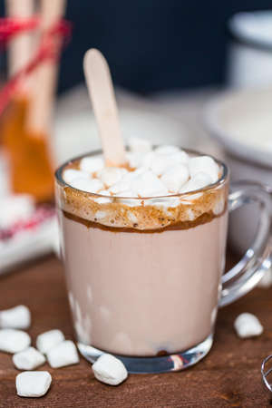 Salted caramel hot cocoa spoon in glass cup topped with marshmallows.