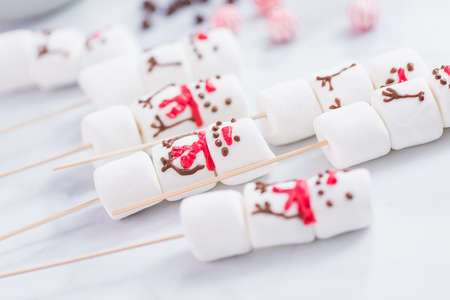 Close up view. Marshmallow snowmen on sticks for hot chocate drink.