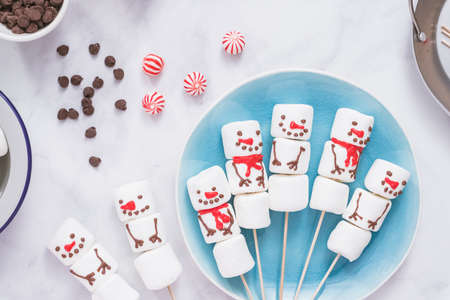 Flat lay. Making marshmallow snowmen and reindeer on sticks for hot chocolate and cocoa drinks.