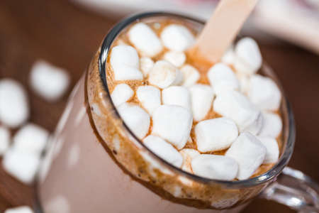 Close up. Salted caramel hot cocoa spoon in glass cup topped with marshmallows.