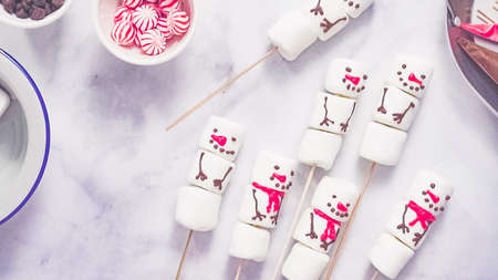Step by step. Flat lay. Making marshmallow snowman and reindeer on sticks hot chocolate toppers for food gifting. Stock Photo