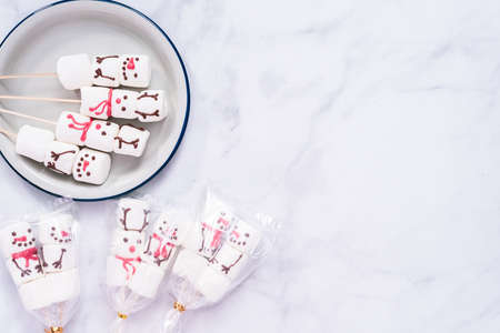 Flat lay. Packaging marshmallow snowmen and reindeer on sticks as small food gifts.