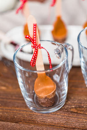Salted caramel hot cocoa spoon in glass cup.