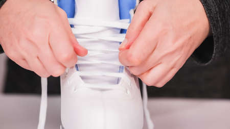 Lacing new white figure skates with white laces.