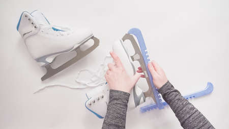 Flat lay. Putting on blue blade guards on white figure skates. Stock Photo