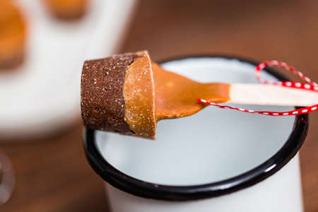 Close up. Salted caramel hot cocoa spoon in metal cup. Stock Photo