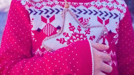 Little girl in red dress holding Christmas ornament on Christmas tree farm.