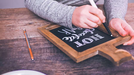 Step by step. Writing chalk board sign-Hot Chocolate Bar- for hot chocolate station. Stock Photo