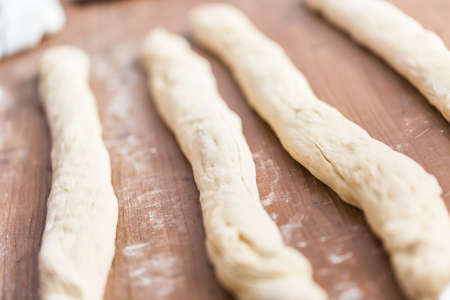 Rolling dough on the wood table to make challah bread. Stock Photo