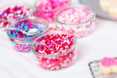 Variety of pink sprinkles for decorating Valentines day cookies.