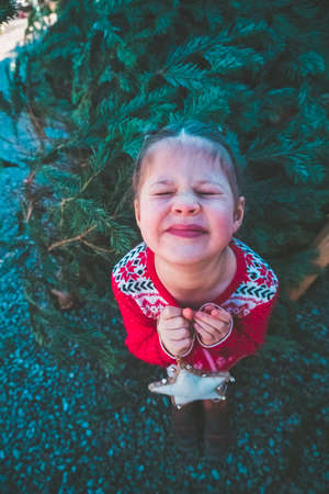 Little girl in red dress on Christmas tree farm. Stock Photo