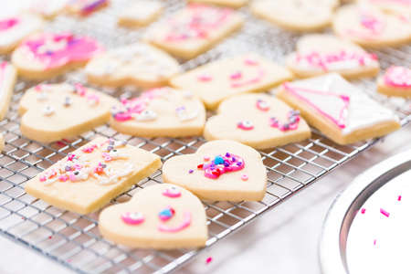 Decorating heart shape sugar cookies with royal icing and pink sprinkles for Valentine's day. 写真素材