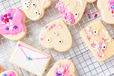 Decorating heart shape sugar cookies with royal icing and pink sprinkles for Valentine's day. Stock Photo