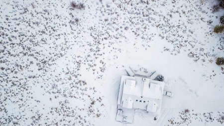Aerial view of the mountain house covered in snow in the Winter. Banque d'images