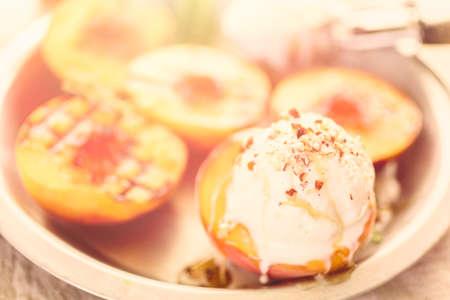 Organic grilled peaches with vanilla ice cream, honey, and pecans. Фото со стока