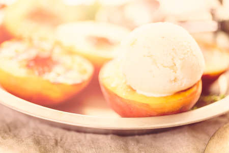 Organic grilled peaches with scoop of vanilla ice cream.
