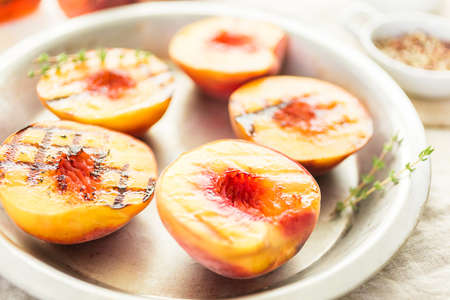 Organic grilled peaches with fresh thyme on a metal plate.