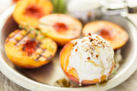 Organic grilled peaches with vanilla ice cream, honey, and pecans. Banco de Imagens