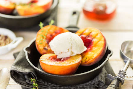 Organic grilled peaches with scoop of vanilla ice cream on a cast iron frying pan. Stock Photo