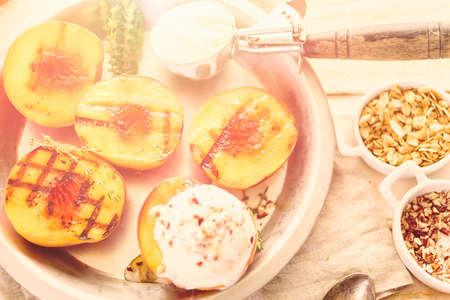 Organic grilled peaches with vanilla ice cream, honey, and pecans. Imagens