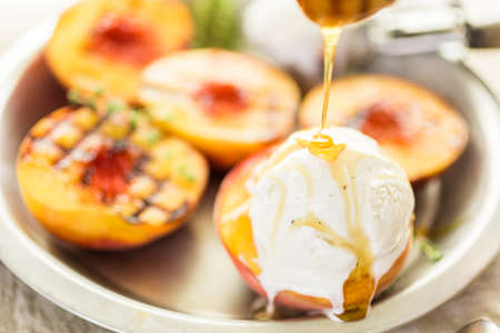 Organic grilled peaches with vanilla ice cream and honey.