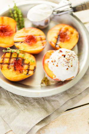 Organic grilled peaches with vanilla ice cream, honey, and pecans. Stock fotó